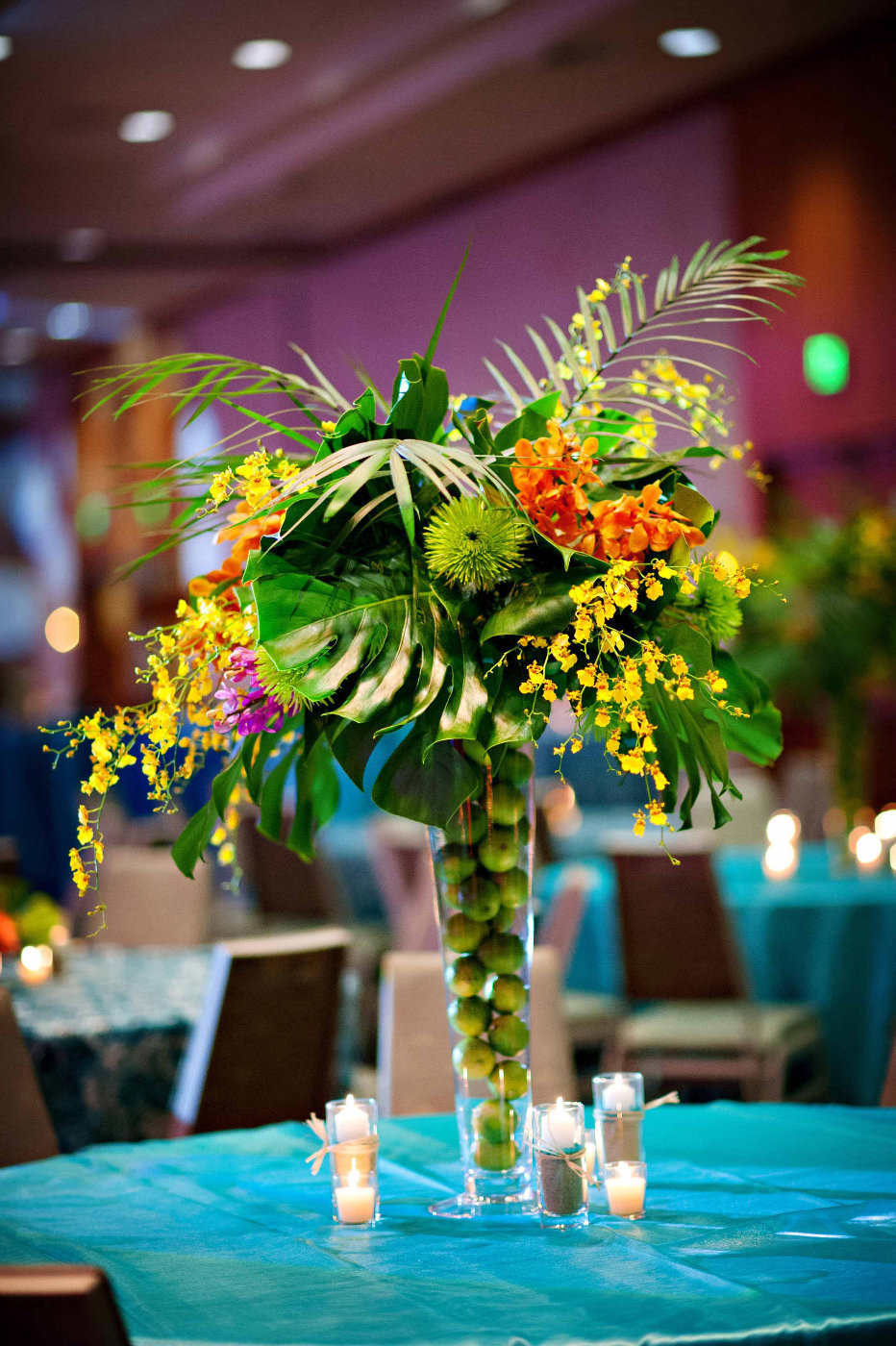 tropical centerpiece with limes, monstera leaves, yellow orchids, ferns, on turquoise linens