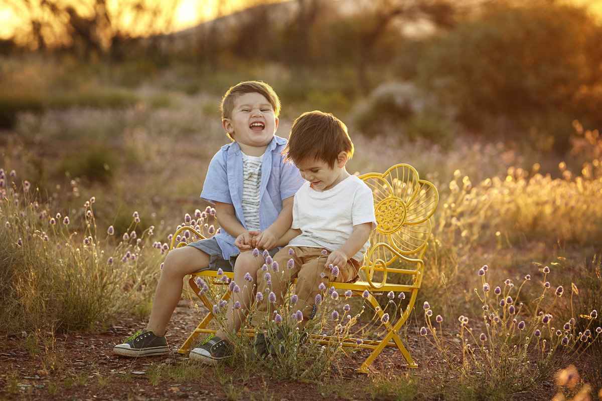 Two boys sitting on yellow chair in a field with golden sunlight