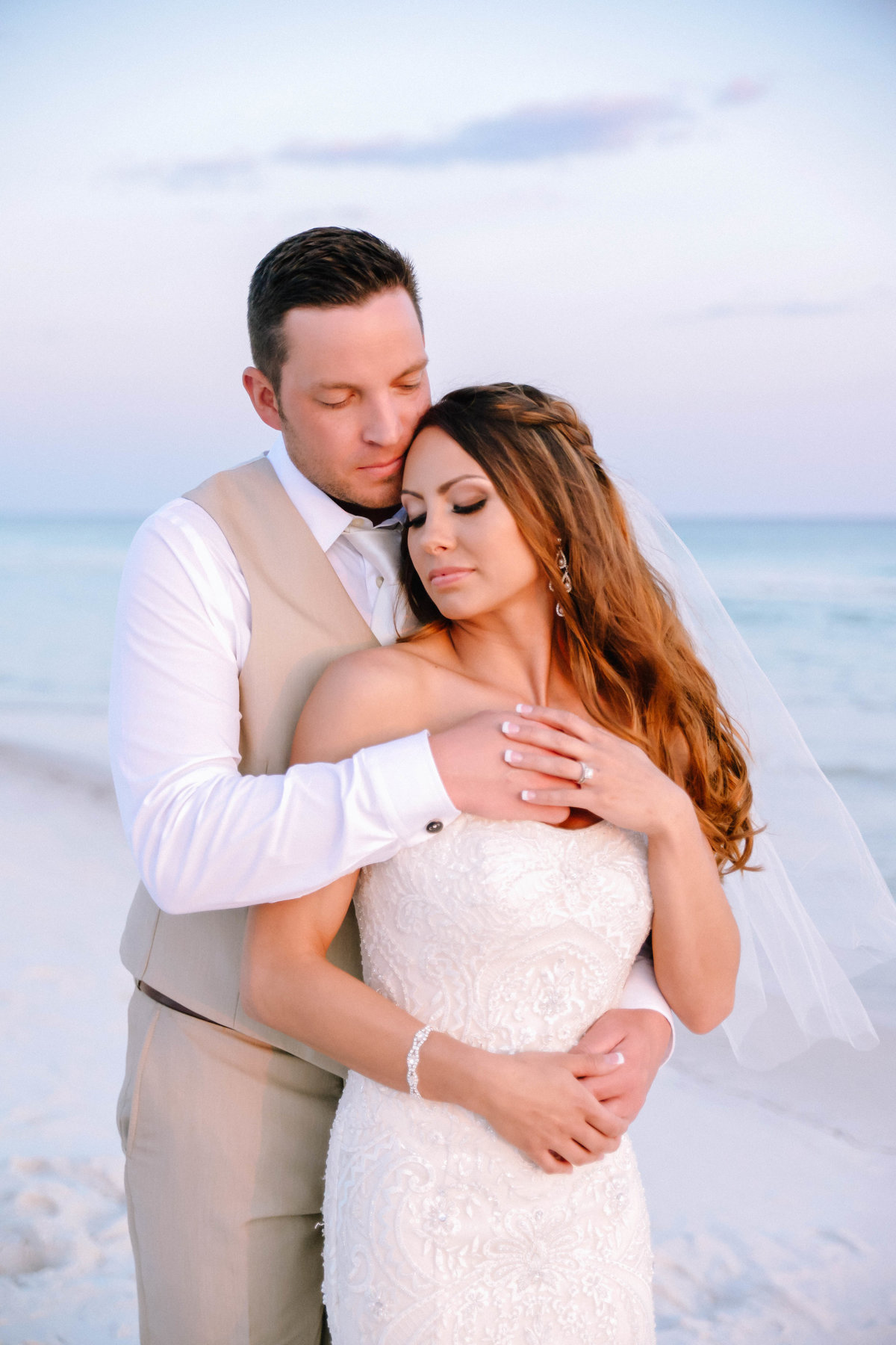 Beautiful bride and her groom holding each other at sunset on the white destin beach sand