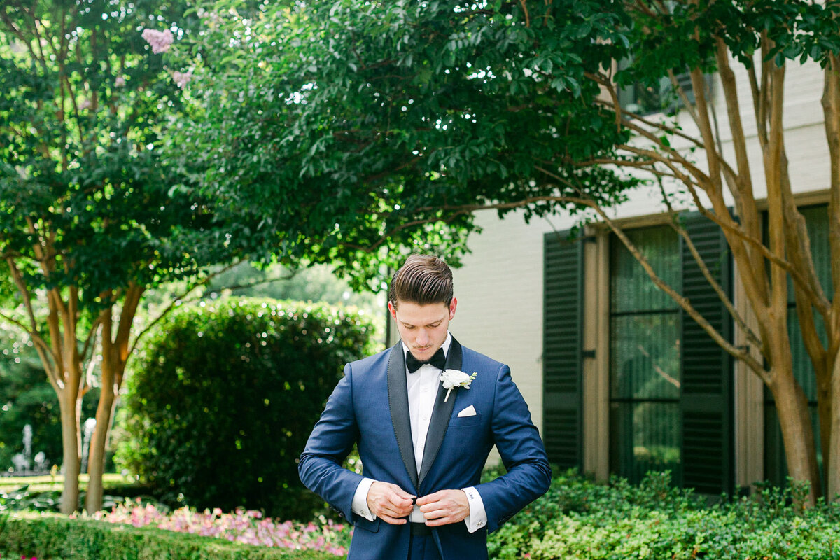 Groom in blue tuxedo buttoning jacket in front of greenery and building