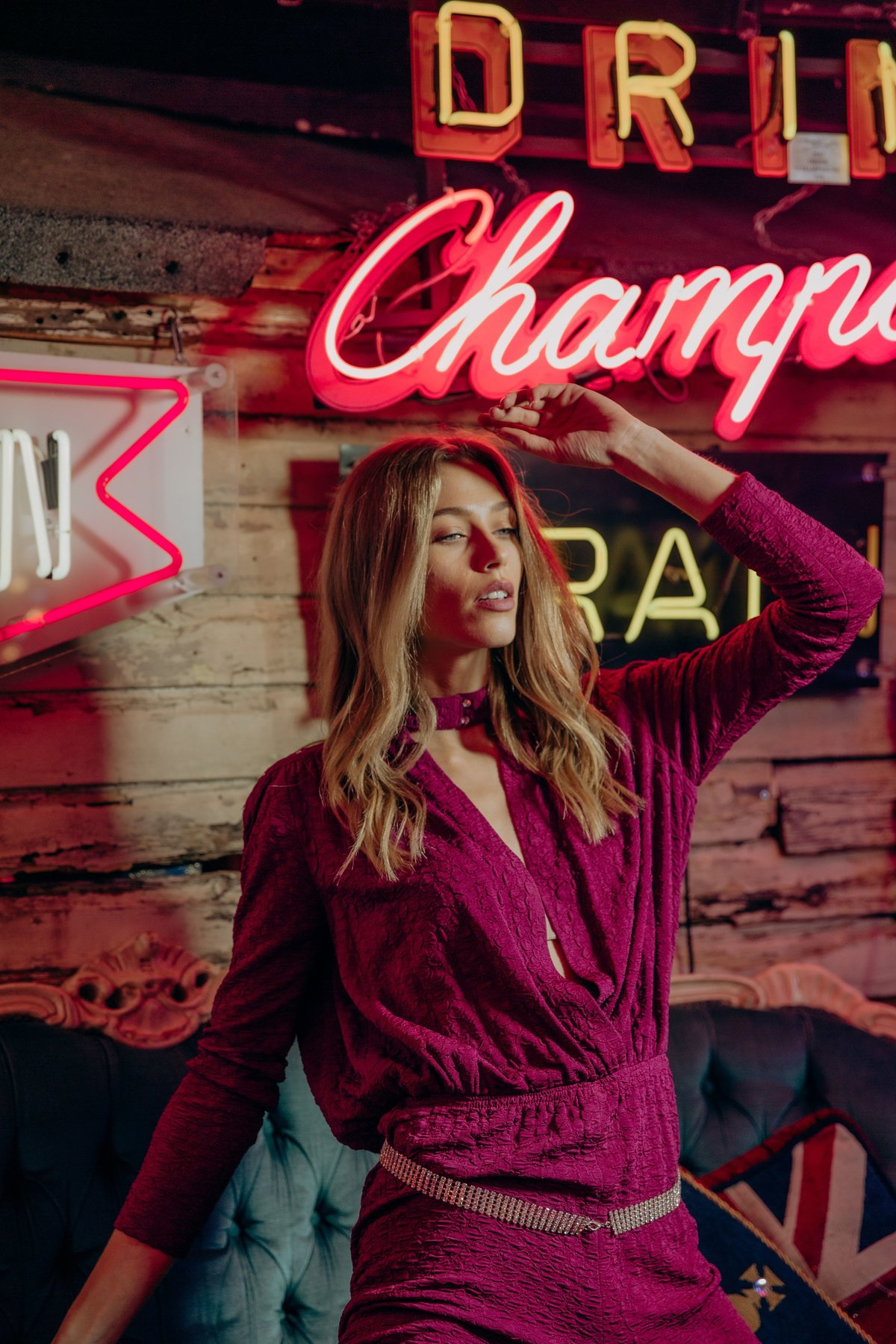 Anastazja wearing a pink jumpsuit kneeling on a blue sofa surrounded by neon signs.