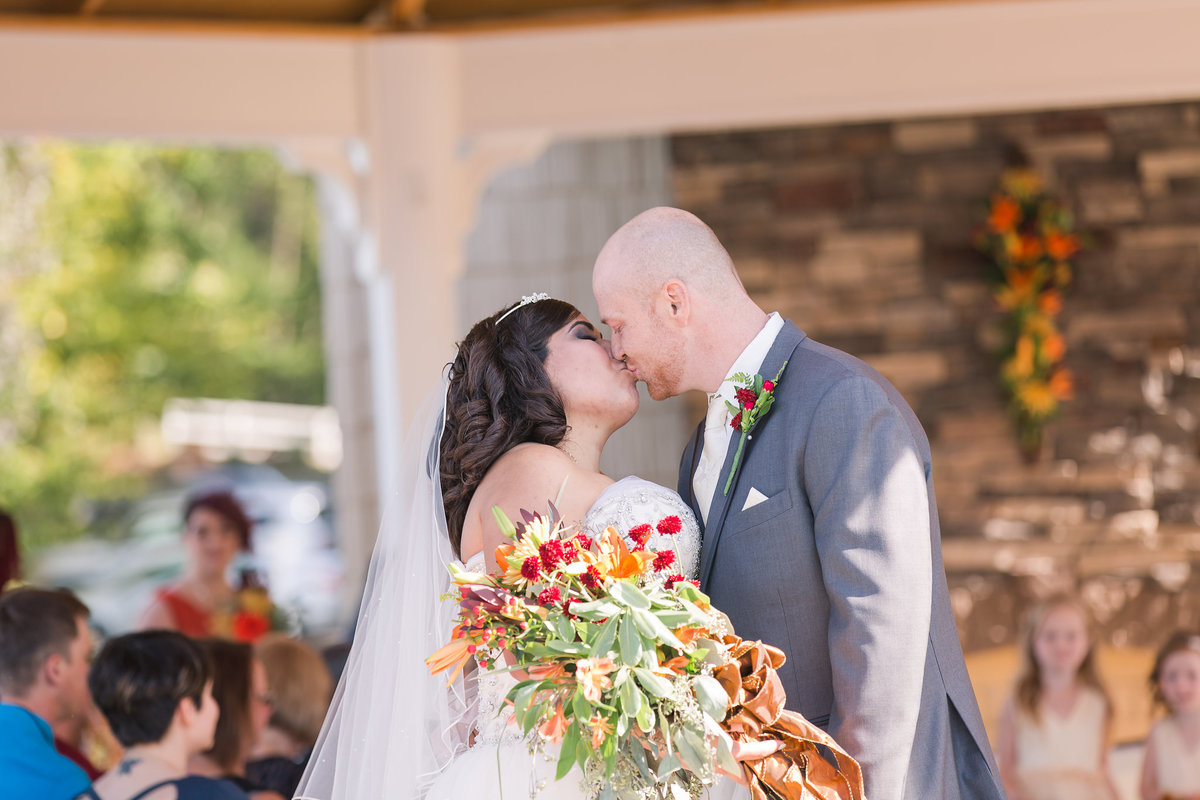 A bride and groom kiss post ceremony at Lake Anna