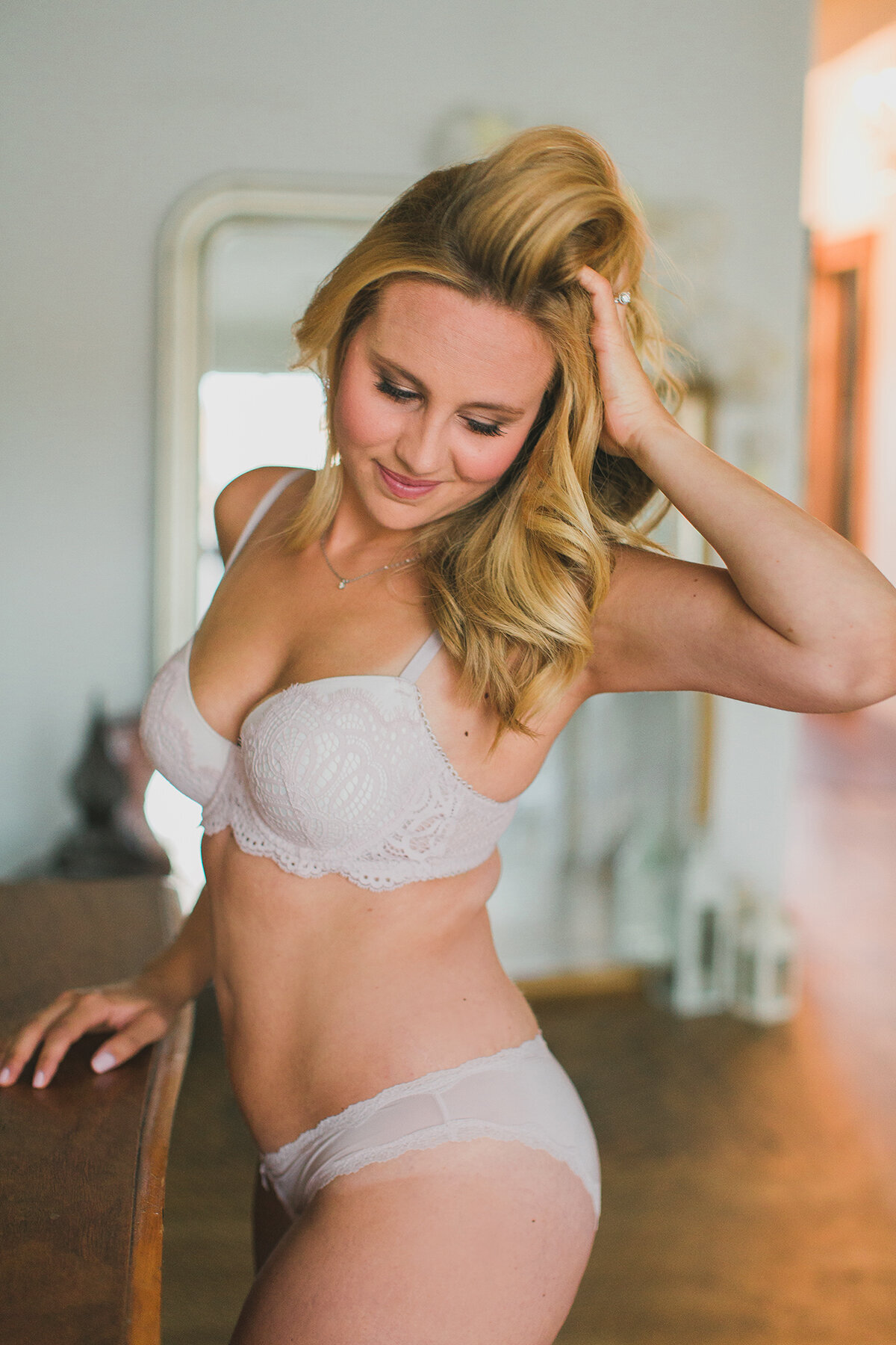 A woman celebrating her postpartum body with a boudoir photo shoot in Chicago.