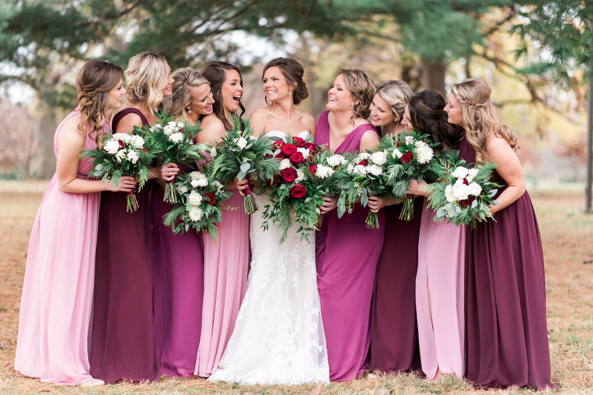 Bride with bridesmaids in forest park for winter wedding.