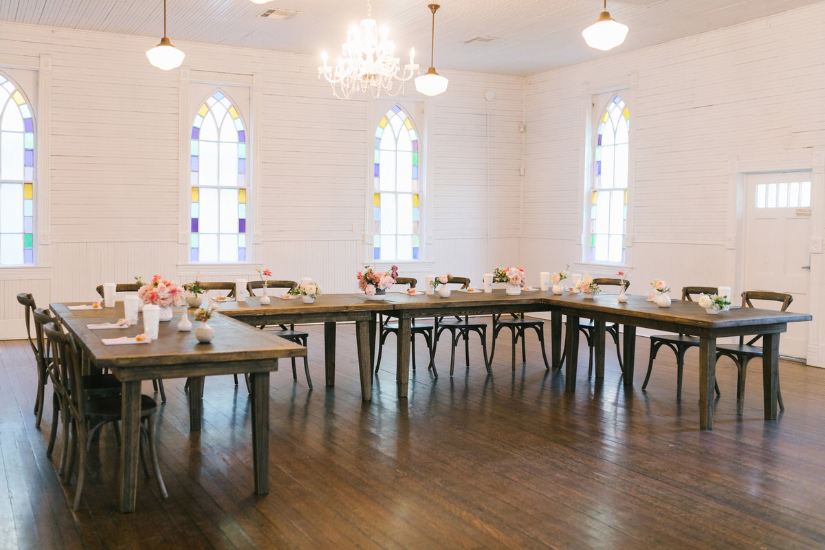 Large open white room with lots of light with wooden tables and chairs set up