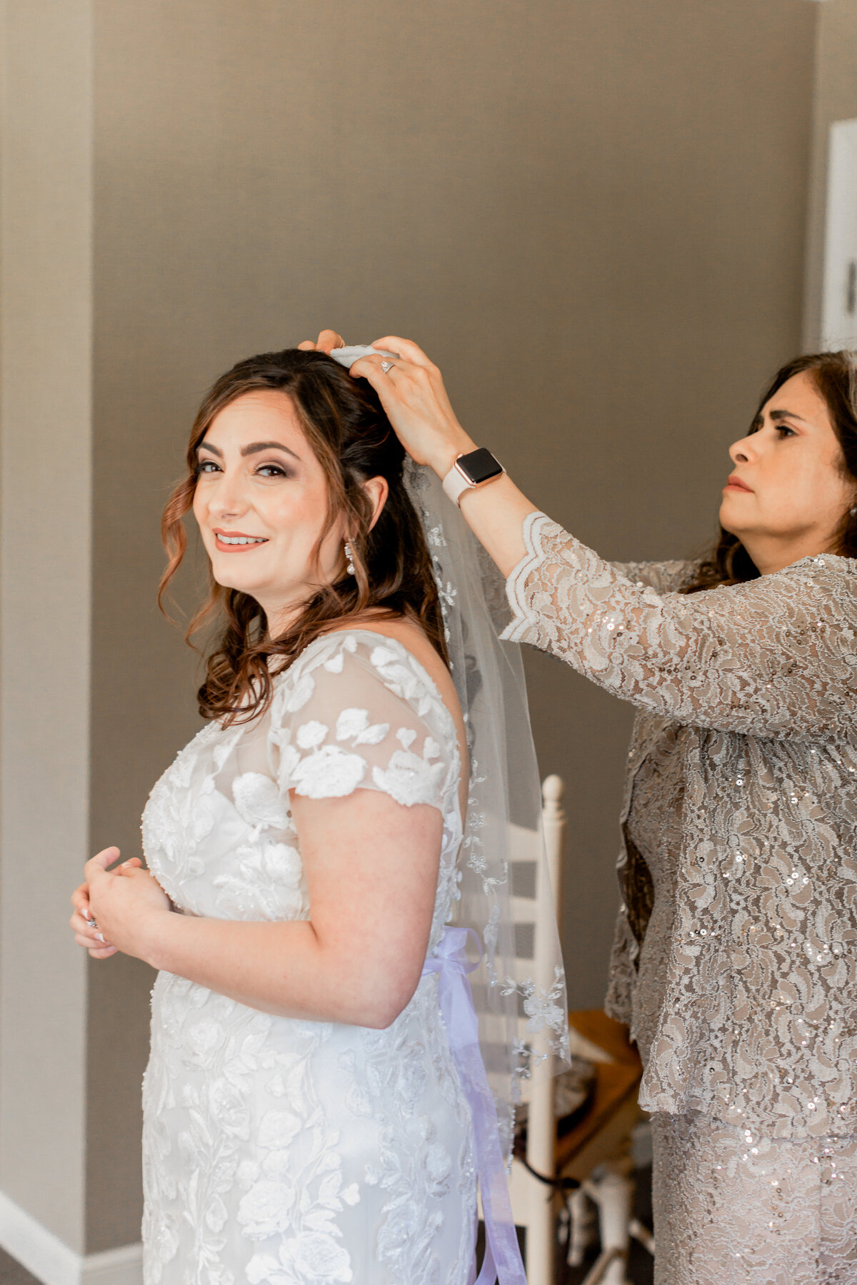 mother putting veil on daughter for wedding