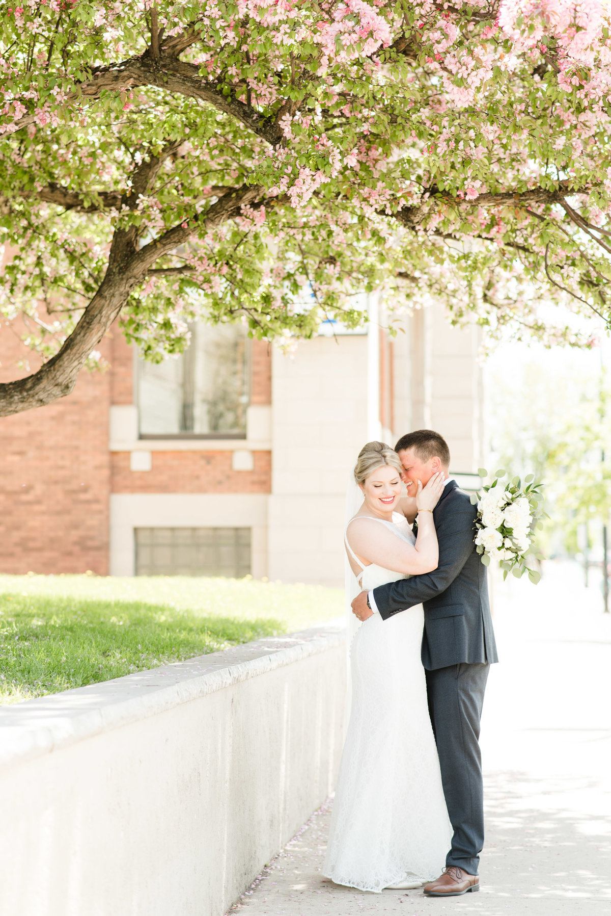 A bride and groom pose under a blossoming tree during their summer wedding in Thunder Bay