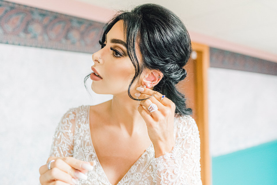 a bride puts on her earrings before the ceremony
