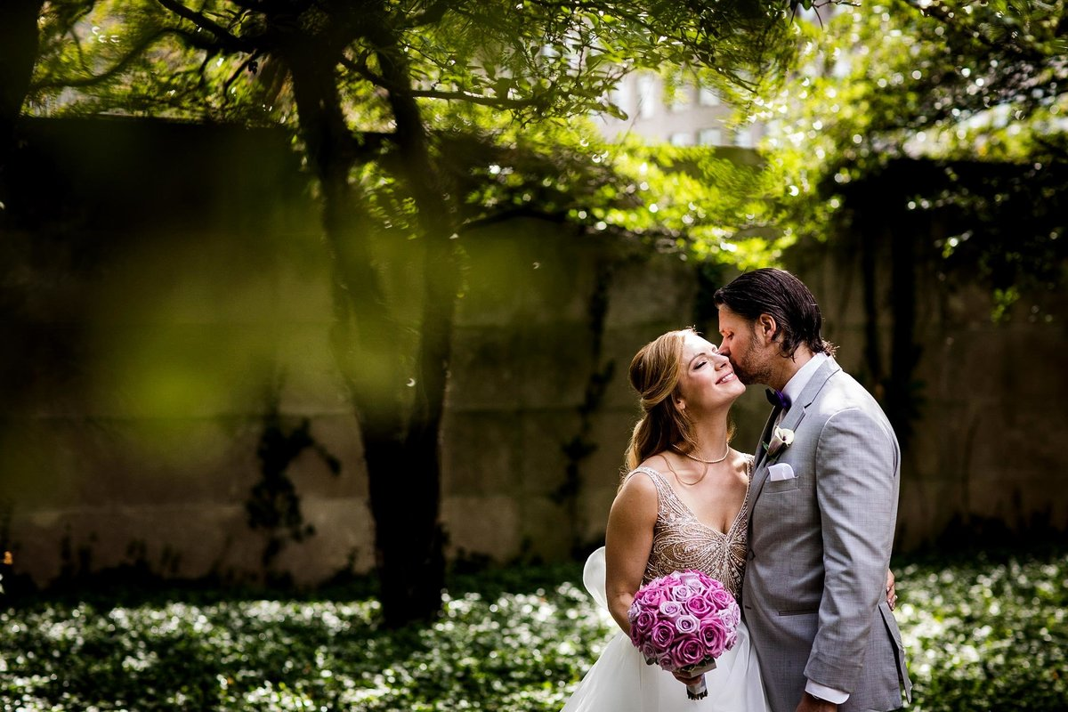 A couple kisses at the Art Institute South Garden during a wedding portrait session.