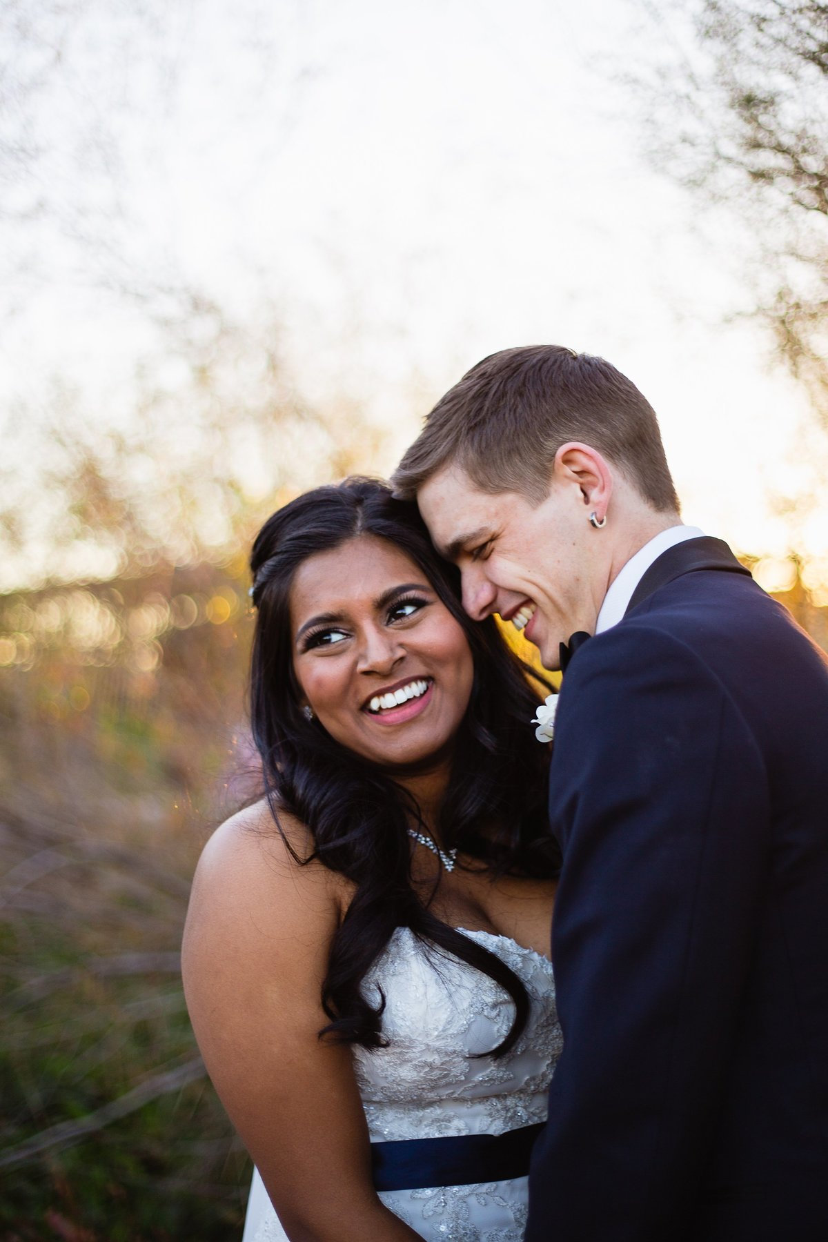 Bride and groom laughing together on their wedding day by Phoenix wedding photographer PMA Photography.