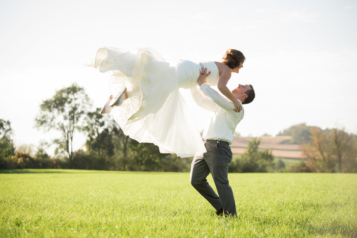 groom lifting bride up in open field