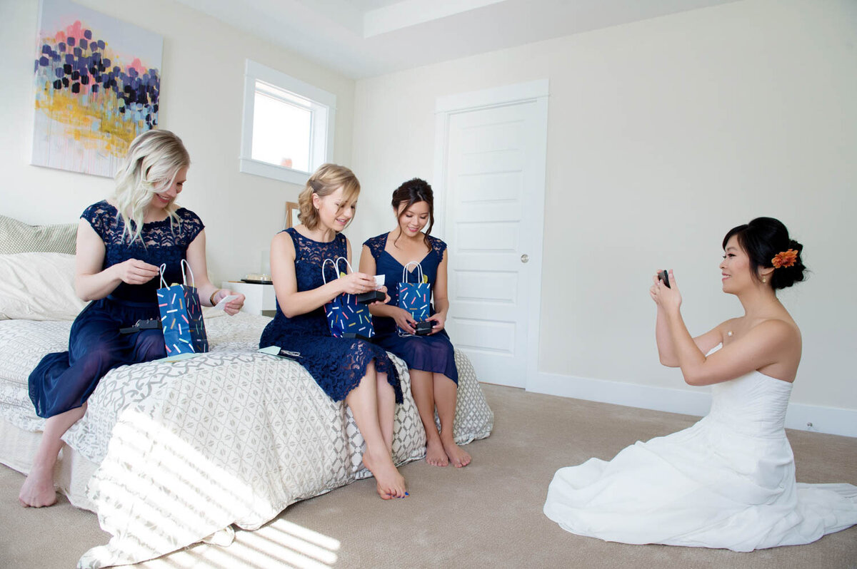 a bride sitting on the floor takes a photo of bridesmaids opening presents