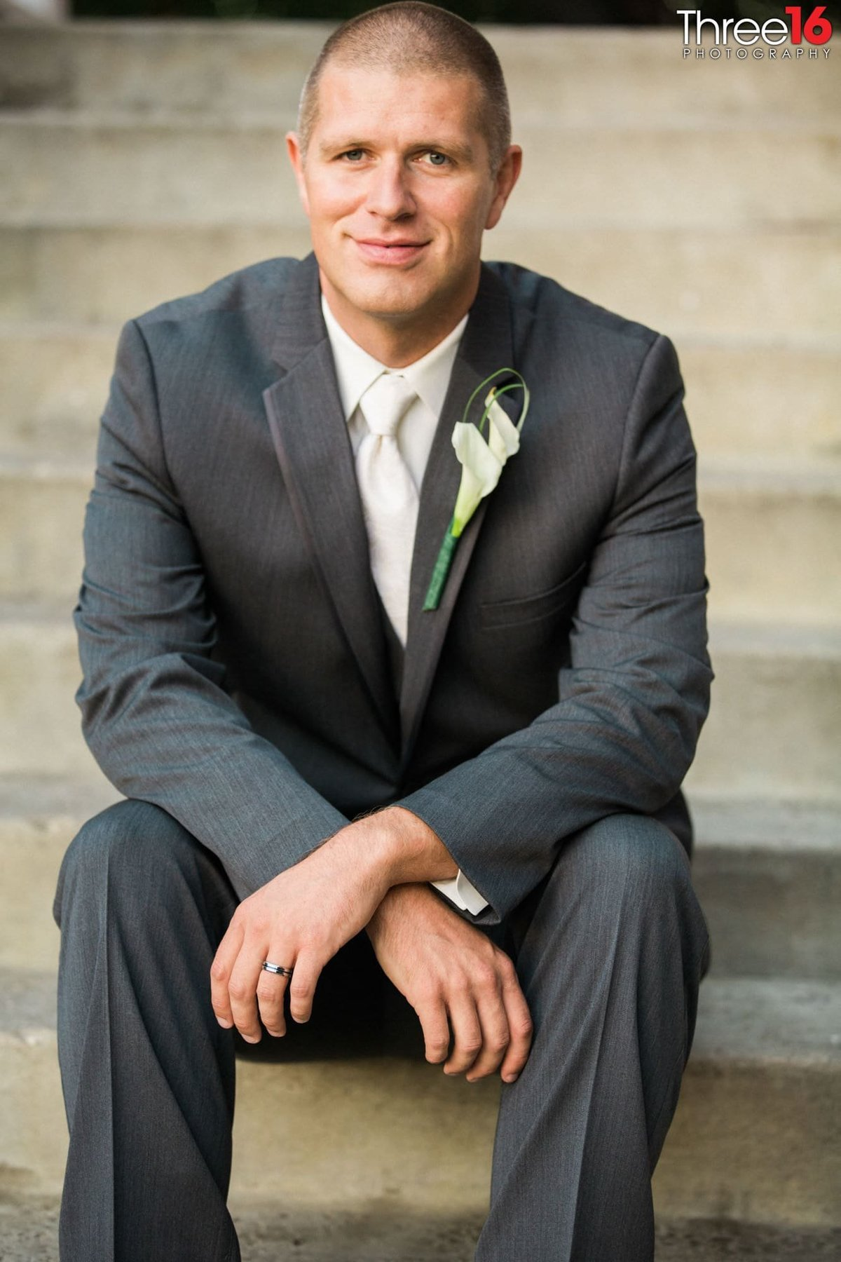 Groom sitting as he poses for the photographer