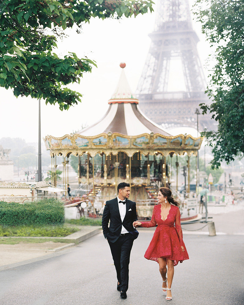 Couple holds hands by carousel in Paris 19