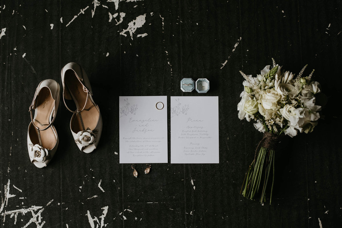 white wedding shoes, white invite, wedding band and engagement ring next to bouquet