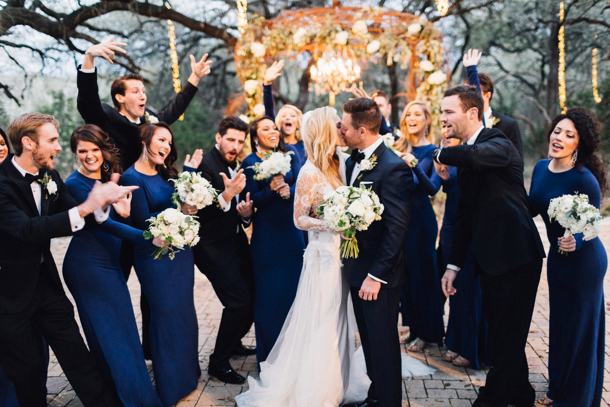 Bride and groom kissing surrounded by joyous bridal party