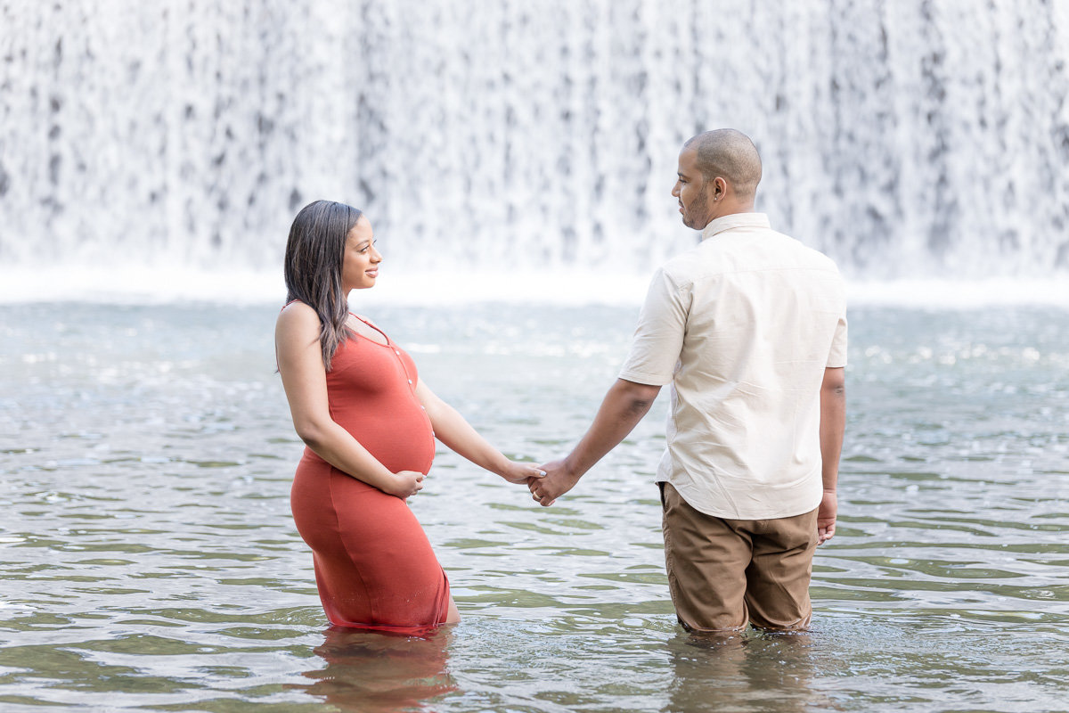 pregnant wife in red dress holds husband's hand in front of waterfall