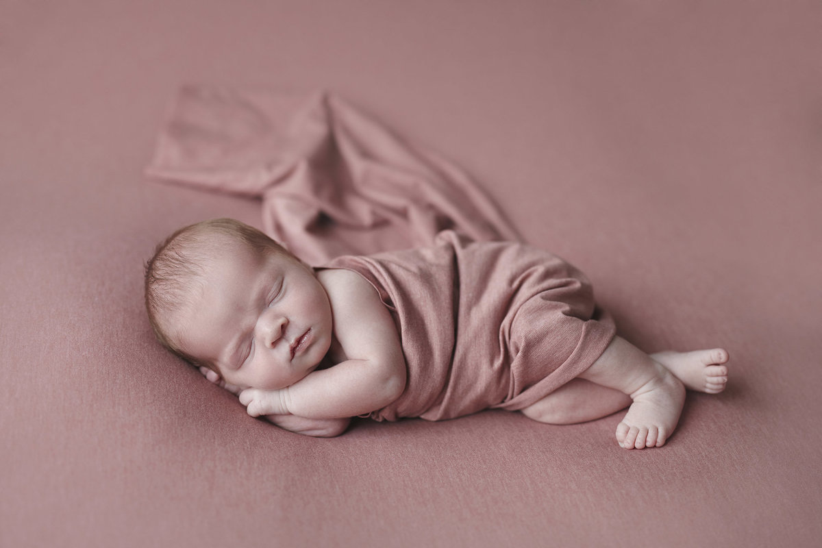 Sleeping newborn girl lying on her side wrapped in a pink blanket on a matching pink blanket