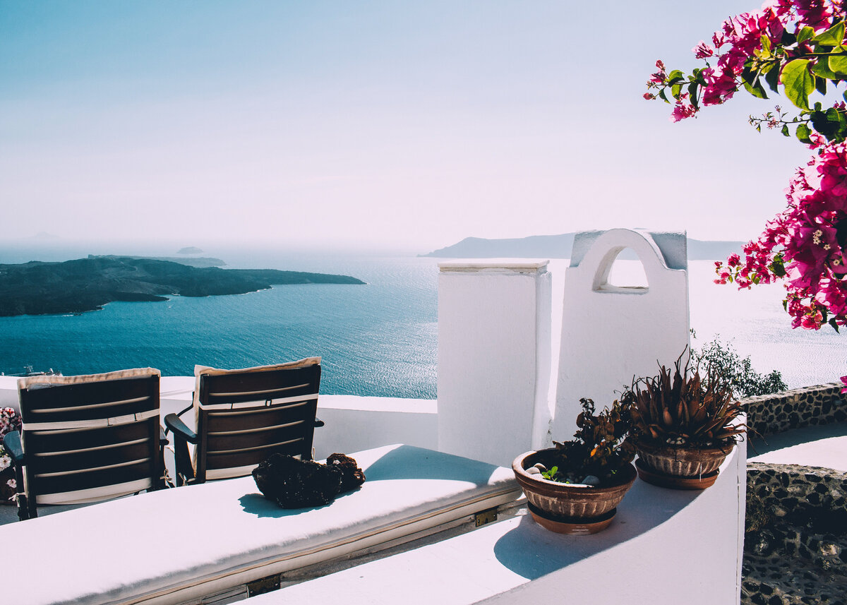 A painted white terrace with two wooden sun lounger overlooking islands in the blue sea in Greece, with bougainvillea