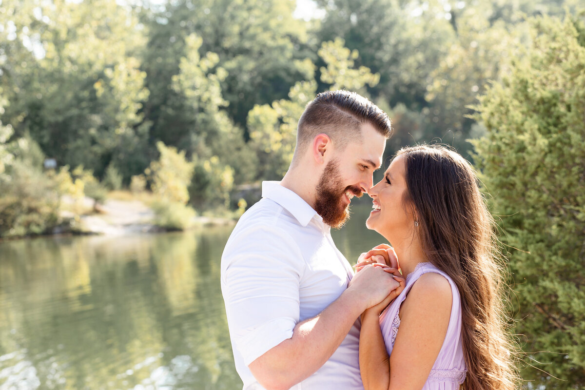 Summer Sunset Romantic Engagement Session in lavender maxi dress couple holding hands looking at each other  by water at Klondike Park in St. Louis by Amy Britton Photography Photographer in St. Louis