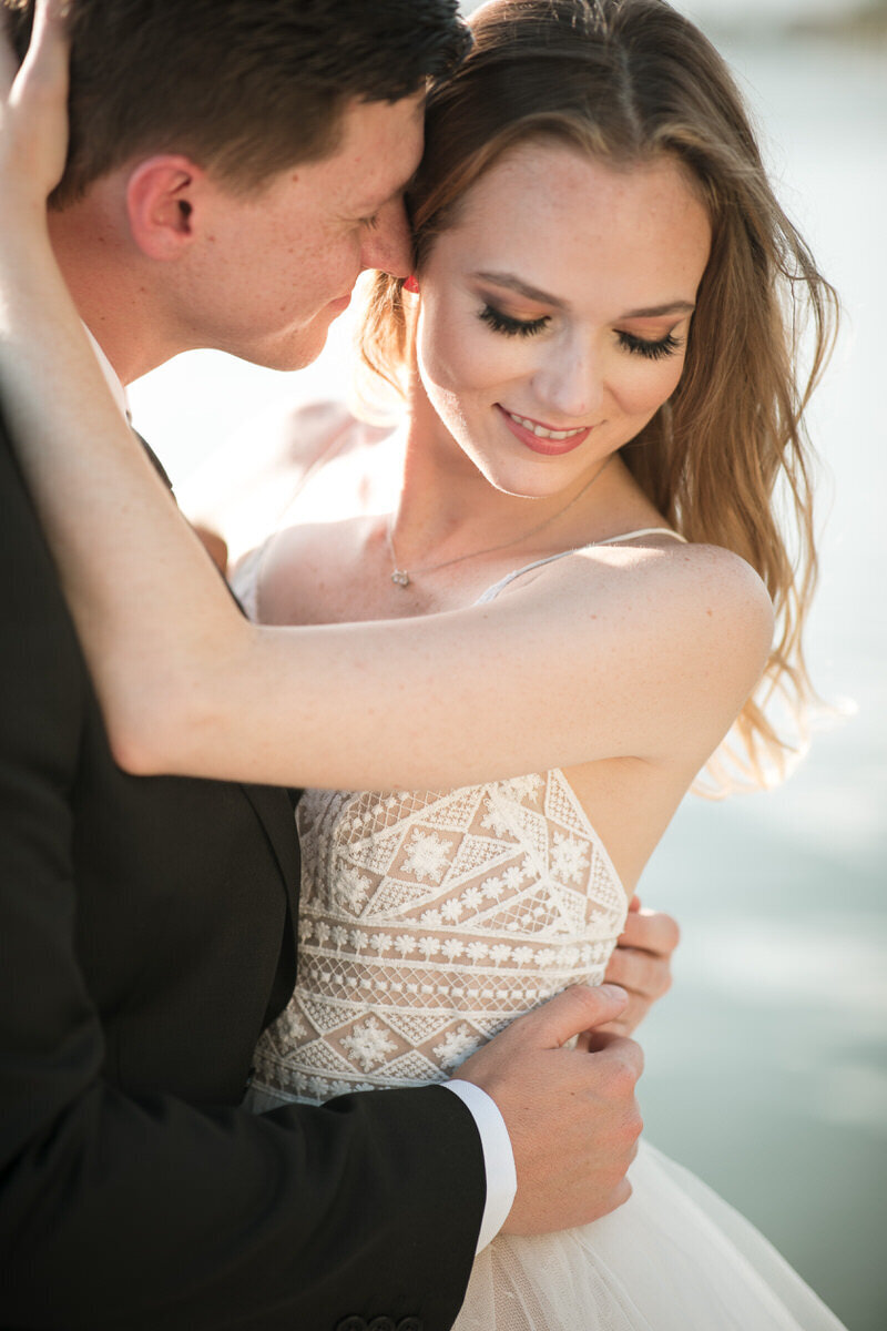 Image of a bride with her eyes closed being embraced by her groom with water in the background