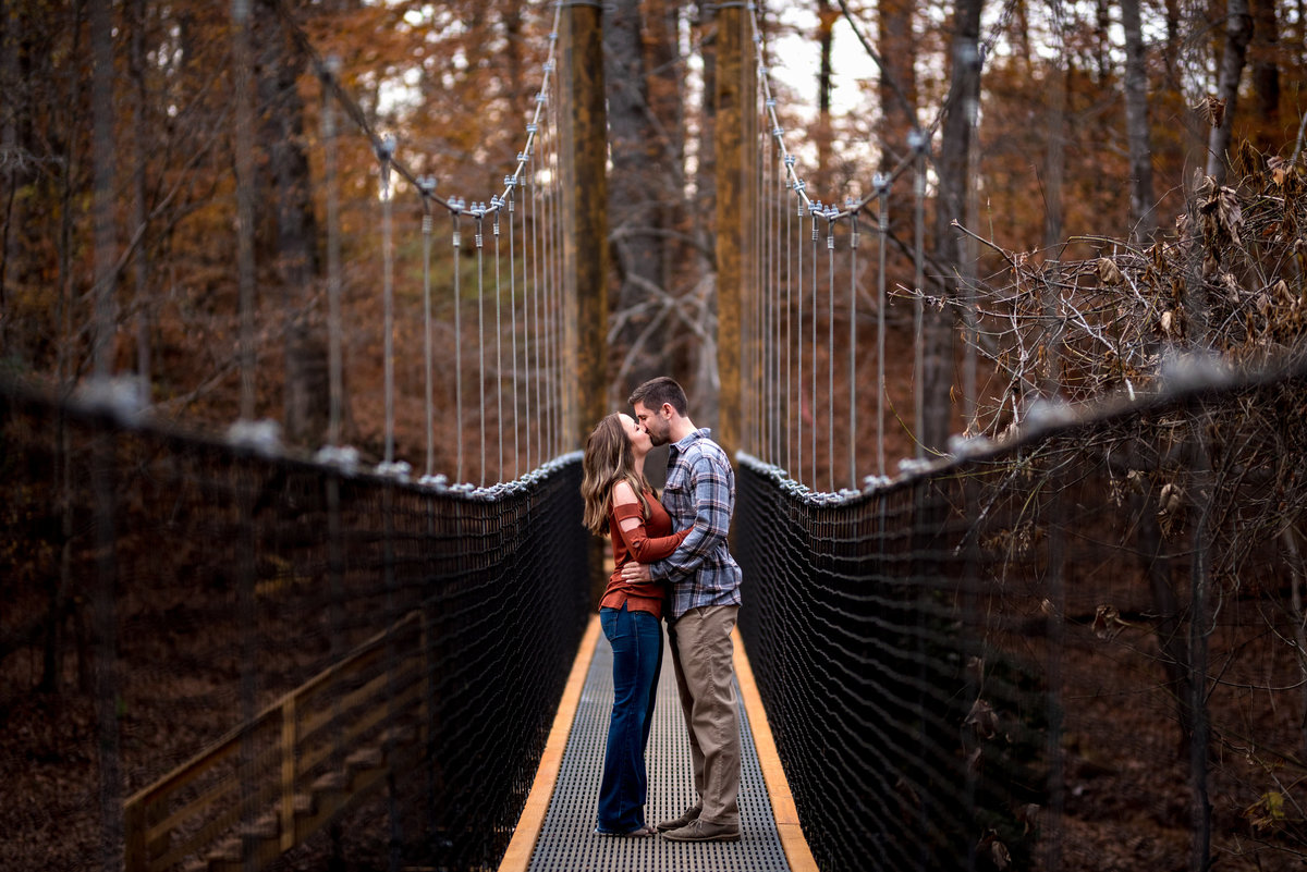 engaged-couple-kiss-on-bridge