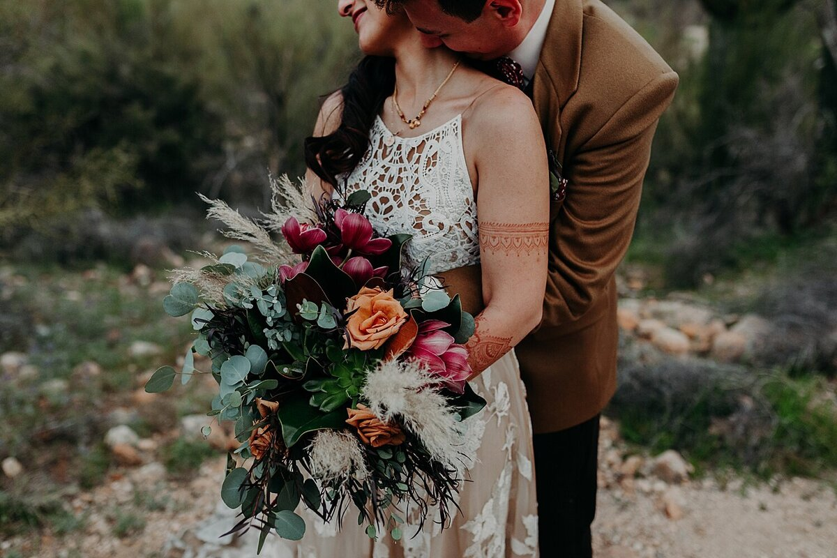 Groom bear hugs bride as she holds a colorful bouquet and he kisses her neck
