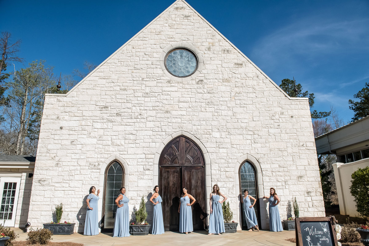 bridesmaid with blue dresses in front of white stone building