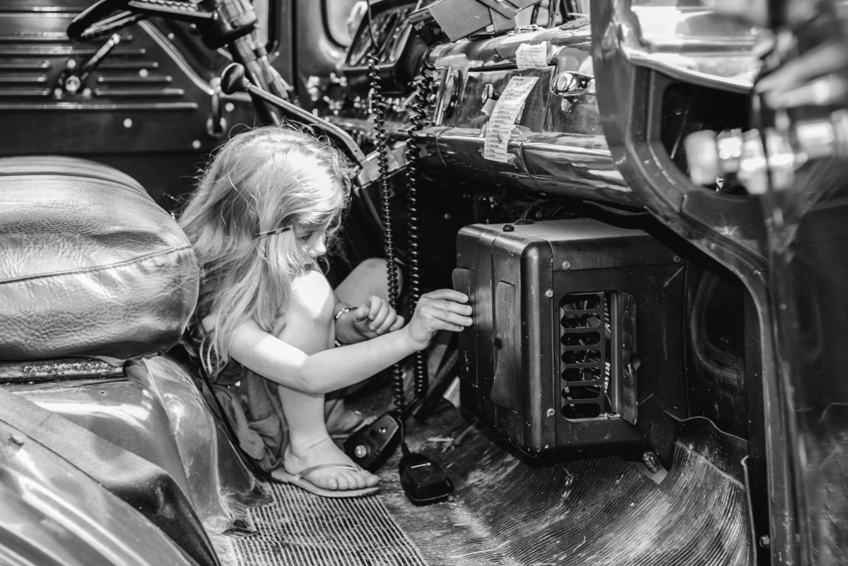 Little girl playing with radio in black and white