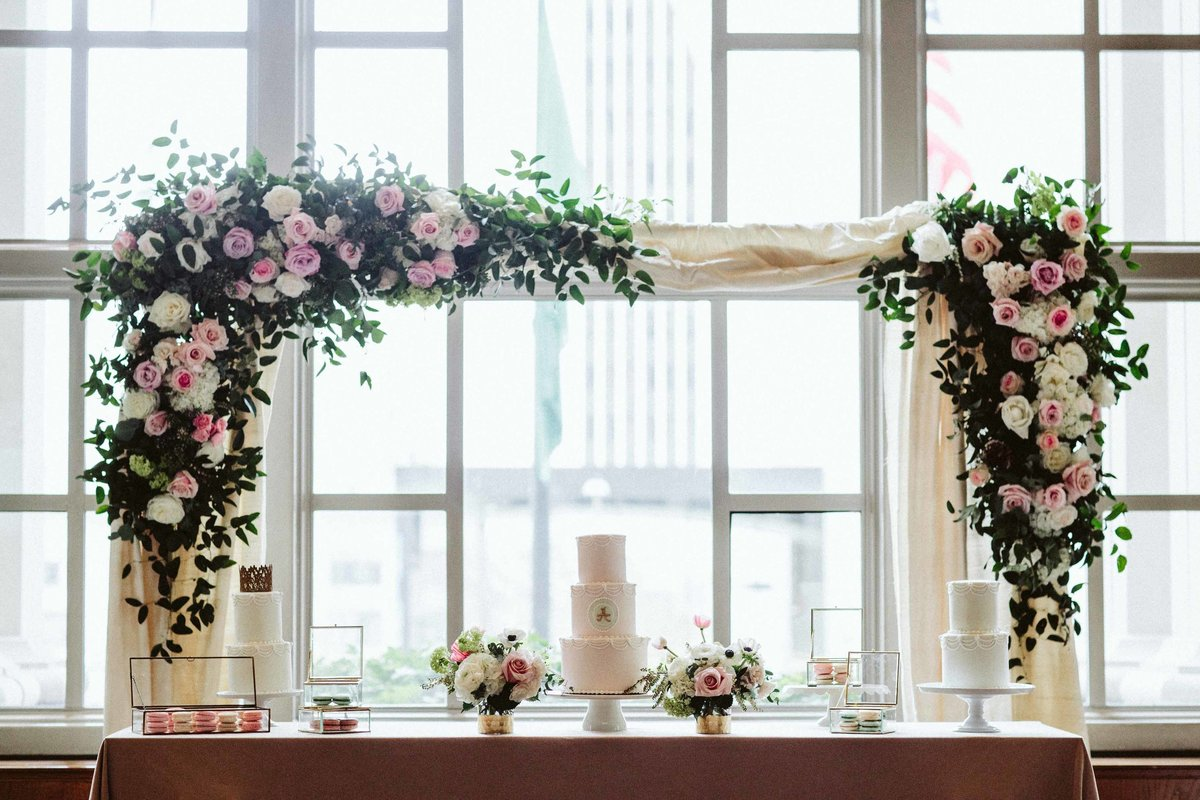Garden party beautiful pink rose arch above cake table.
