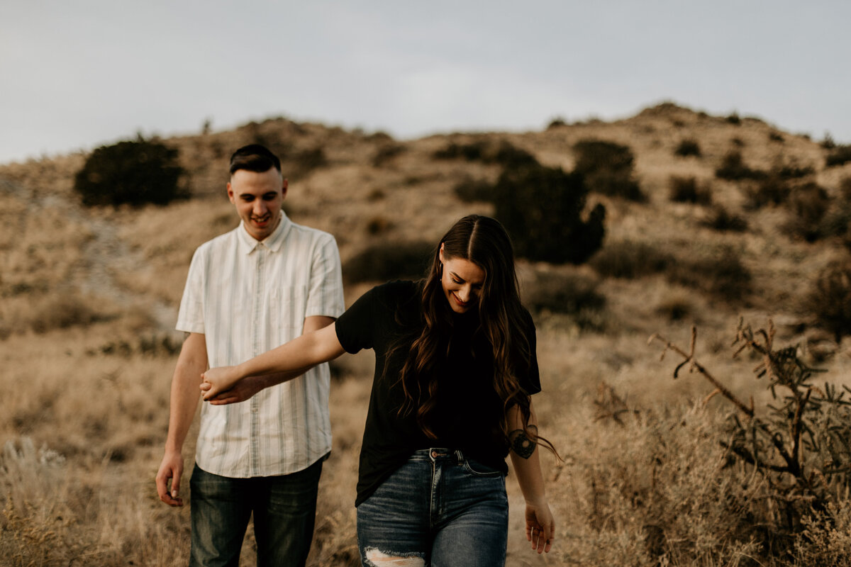 engaged couple holding hands and walking in the desert