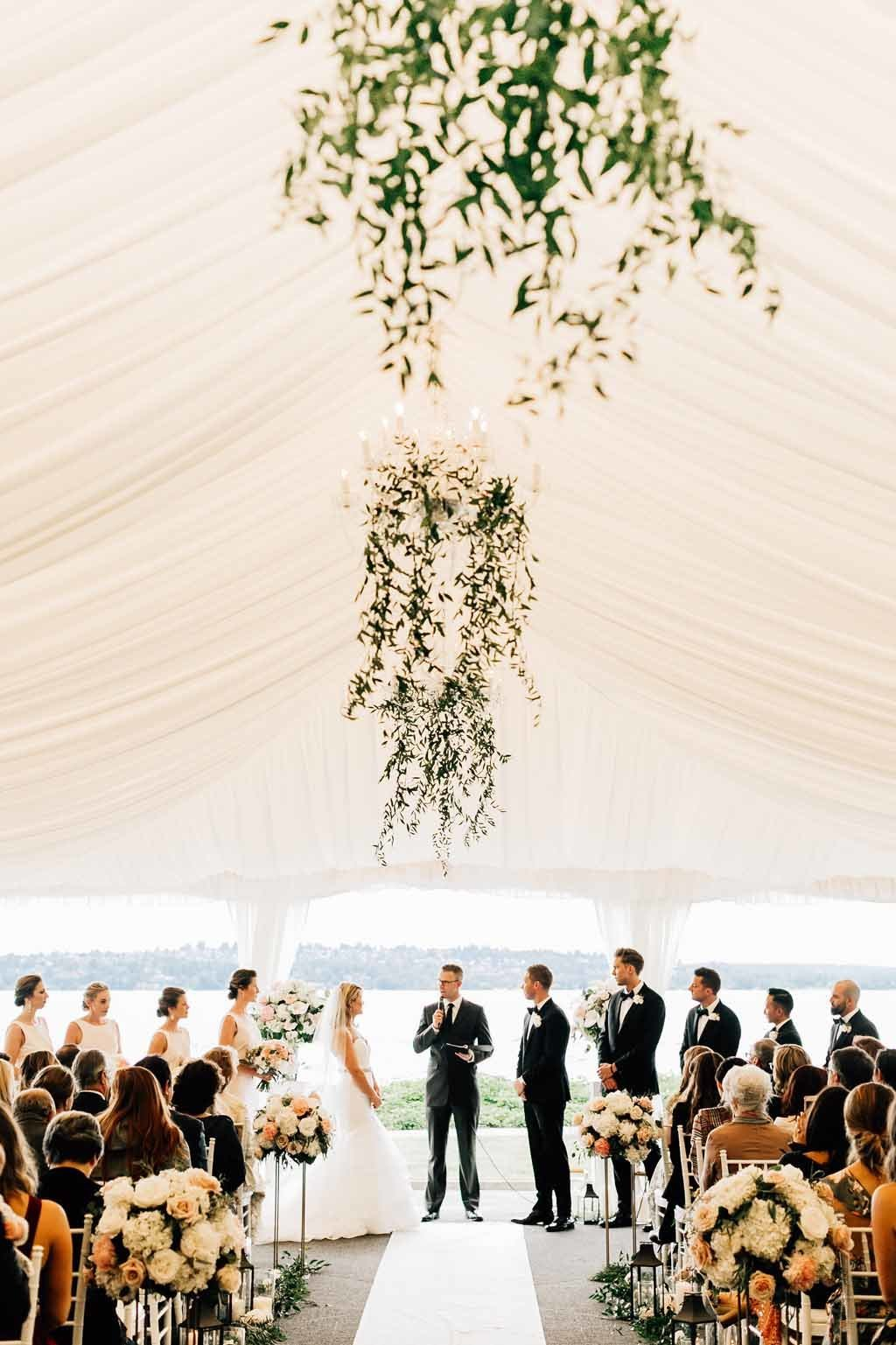 Greenery covered chandeliers suspended above the aisle for the tent wedding ceremony.