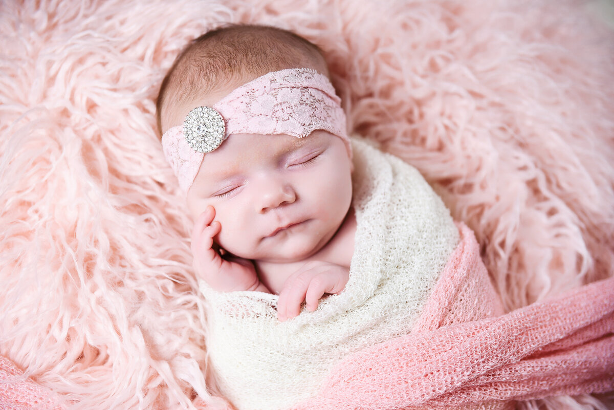 Beautiful Mississippi newborn photography: newborn girl wrapped in pink, ivory and rhinestones in Mississippi