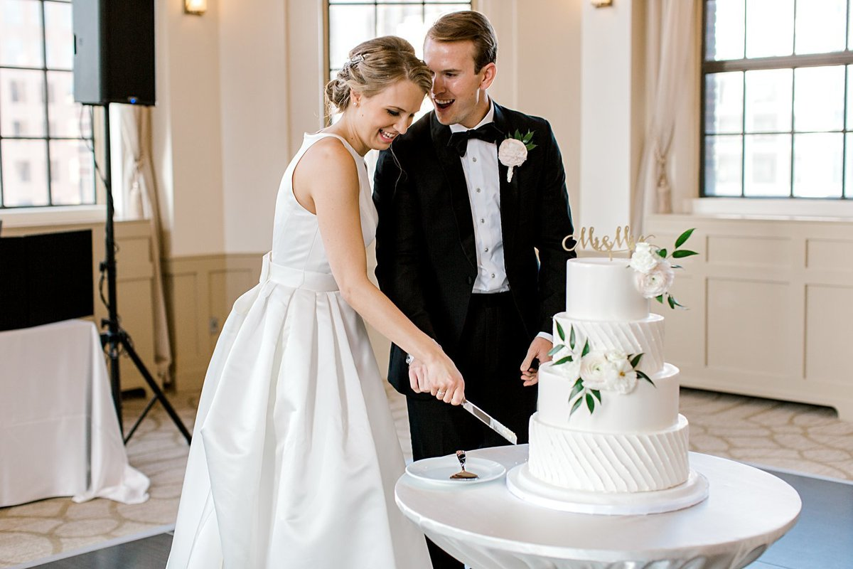 couple cutting wedding cake during reception at the warwick allerton top top tap ballroom on their wedding day