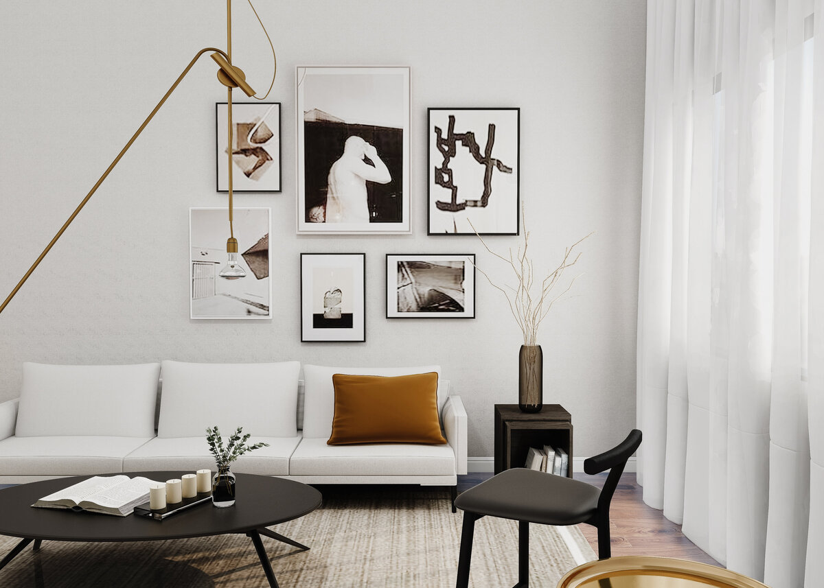 A monochrome modern lounge is styled with a gallery wall and a white sofa and a burnt orange accent cushion.