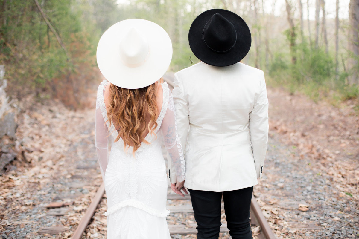 trendy bride and groom in black and white hats pose outdoors