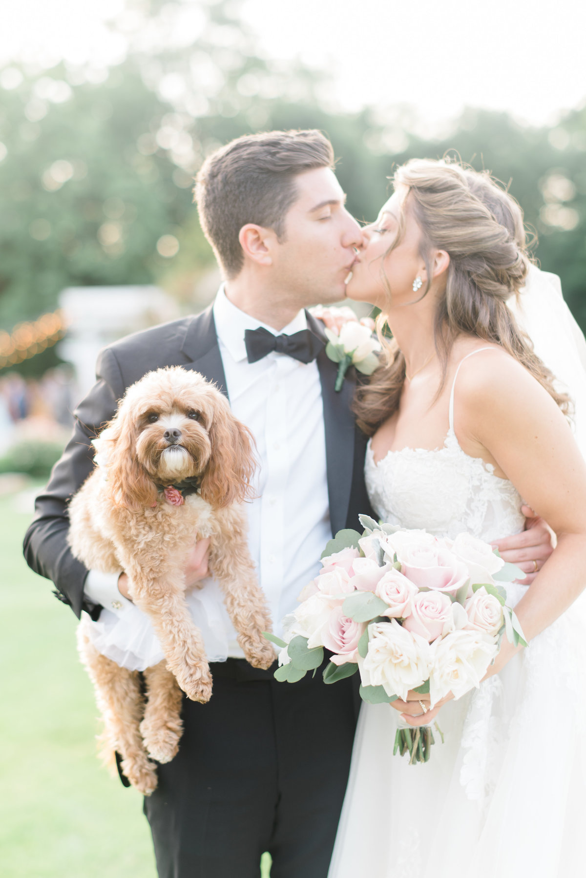 portrait-bride-and-groom-kissing-wit-groom-holding-dog