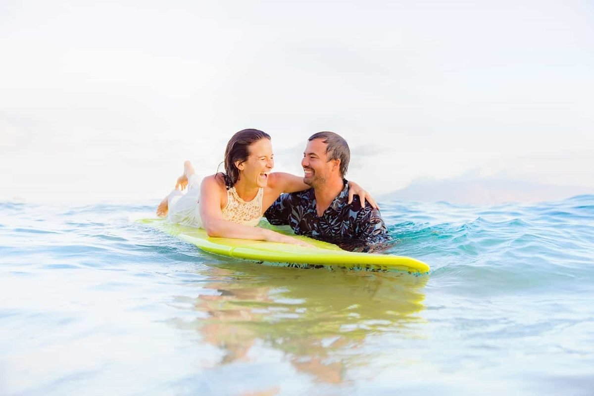 Couple laughing with a yellow surfboard in the water