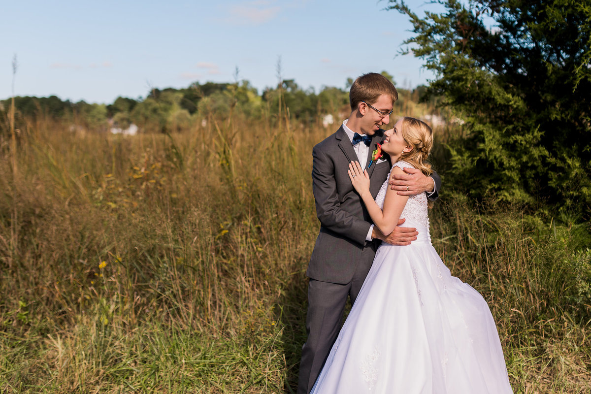 A bride and groom stand in front of the water at Fort Eustis