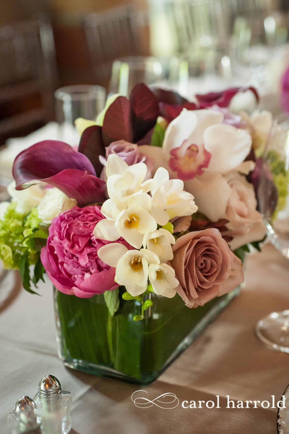 modern centerpiece of white freesia, pink peonies, purple calla lilies, mauve roses, white orchids, in leaf lines square glass vase