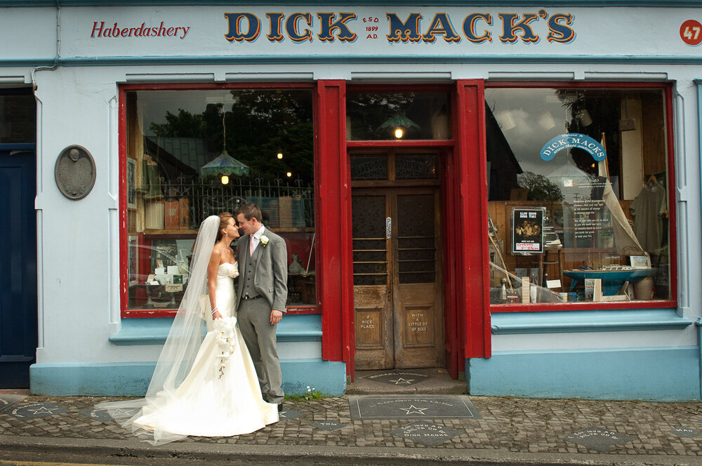 bride wearing a trumpet style wedding dress with corset top with groom wearing a light grey coat tail jacket outside Dick Mack's pub in Dingle