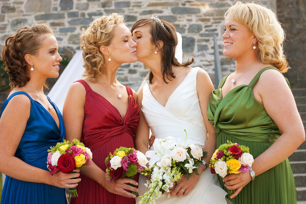 bride with v-neck, a-line, layered tulle dress kissing one of her bridesmaids who are wearing wine, blue and green dresses
