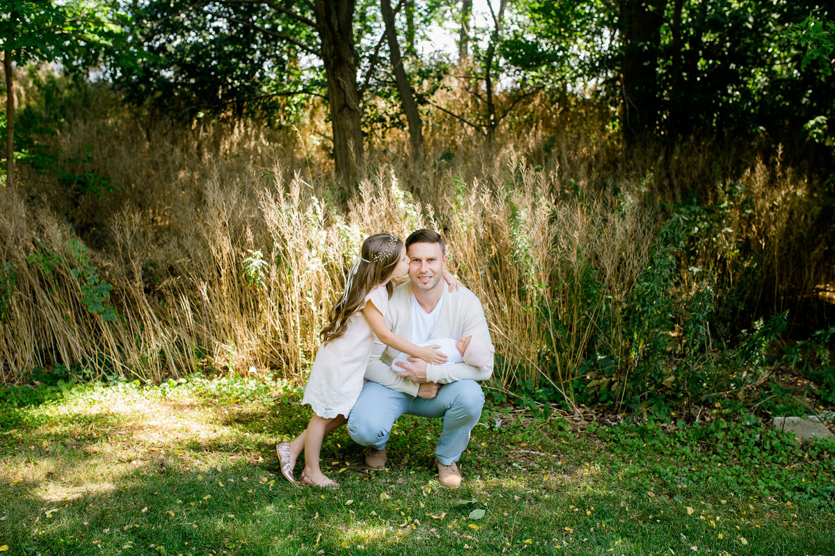 Daughter kissing father while he holds newborn baby girl outdoors {Oakville Family Photographer}