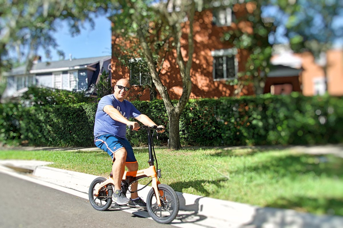 Man riding Orange Go-Bike M4 in his neighborhood