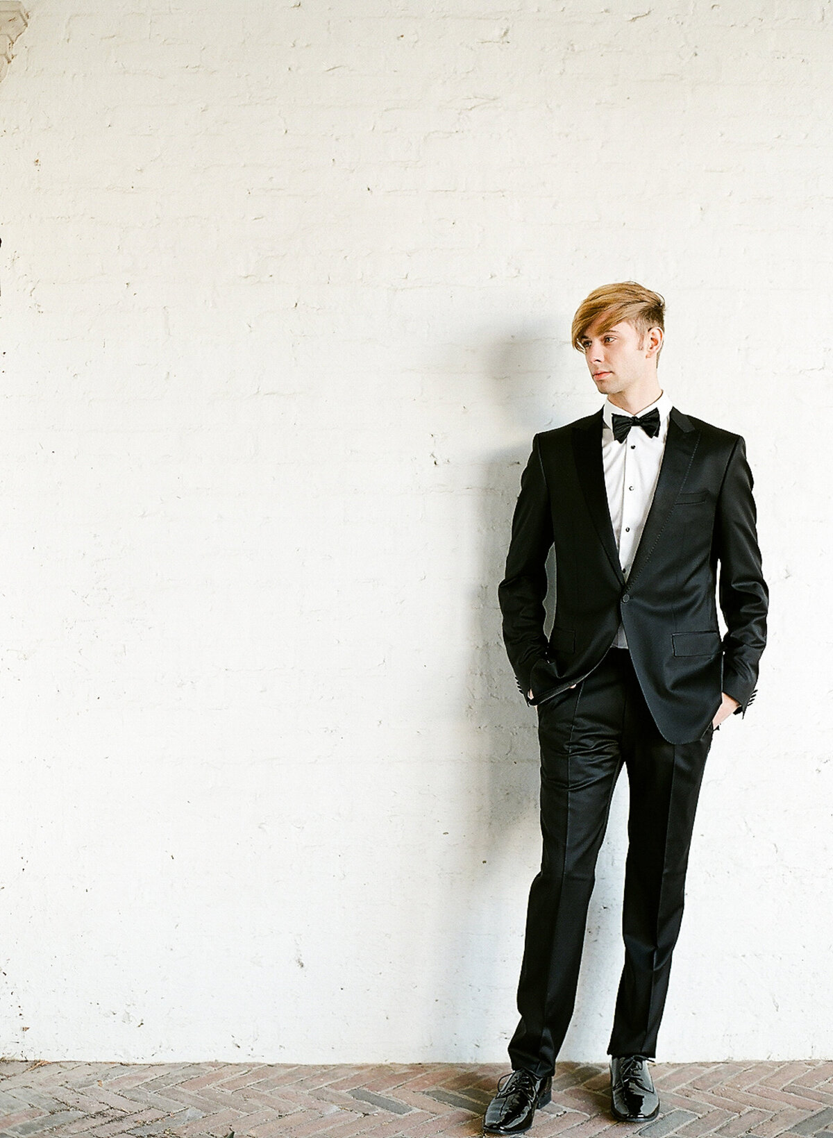 Groom in tux standing against white wall
