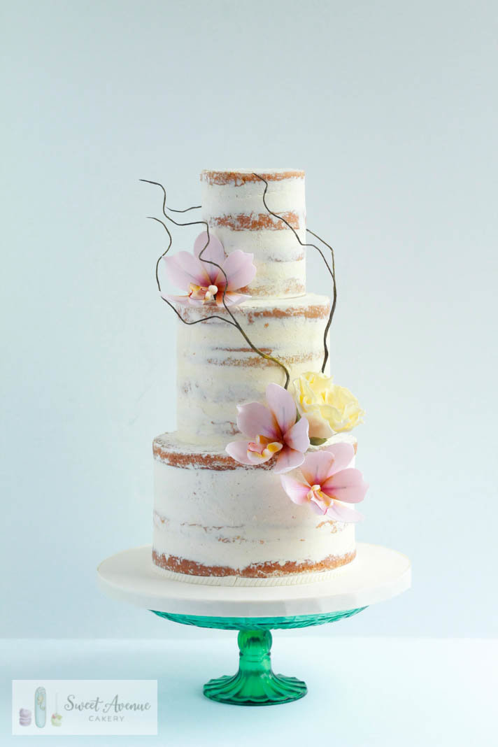 rustic semi naked buttercream wedding cake with blush sugar orchids
