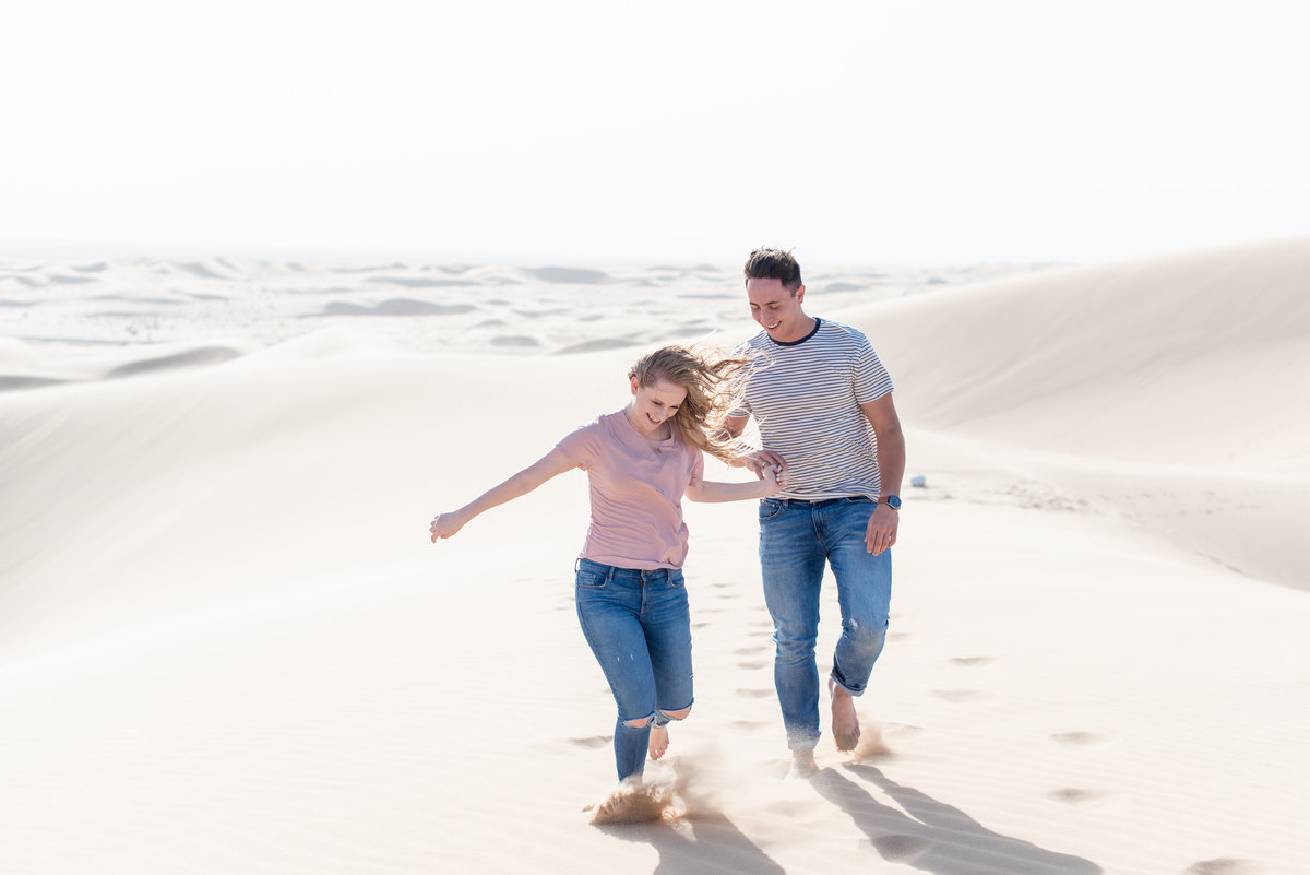 A girl and a boy are running through the sand holding hands at Glamis Sand Dunes
