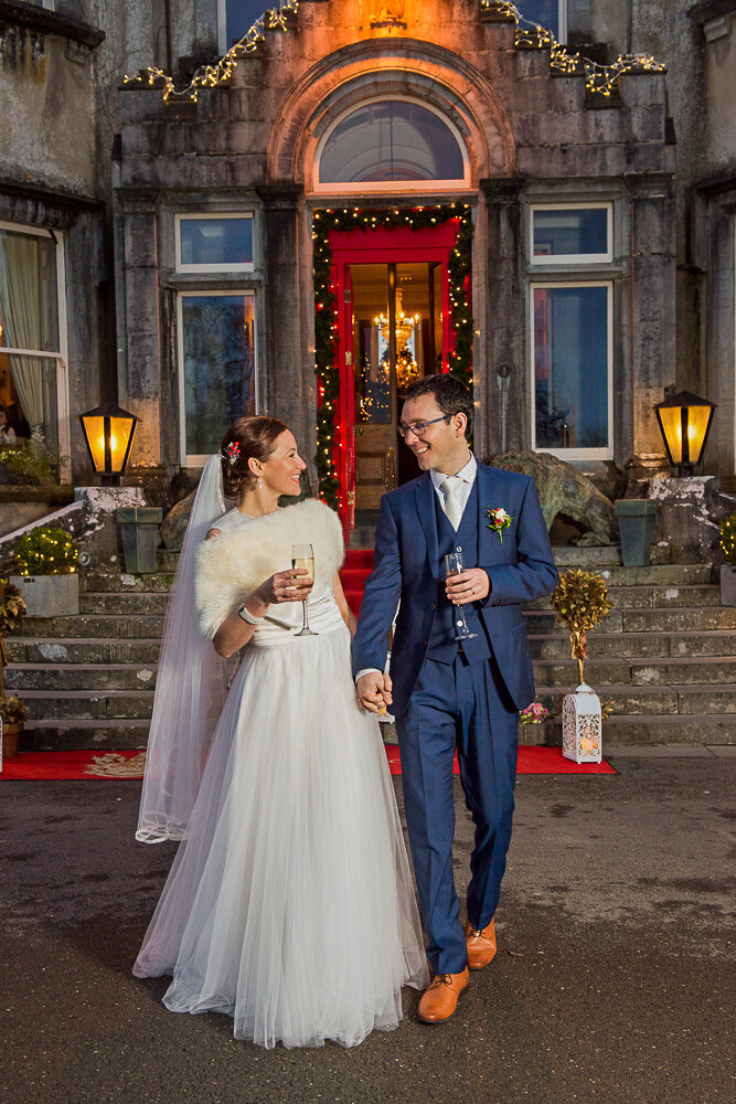 bride in a luxuriant style tulle wedding dress walking with groom in a navy suit and brown shoes, holding champage in front of Ballyseede Castle with Christmas lights