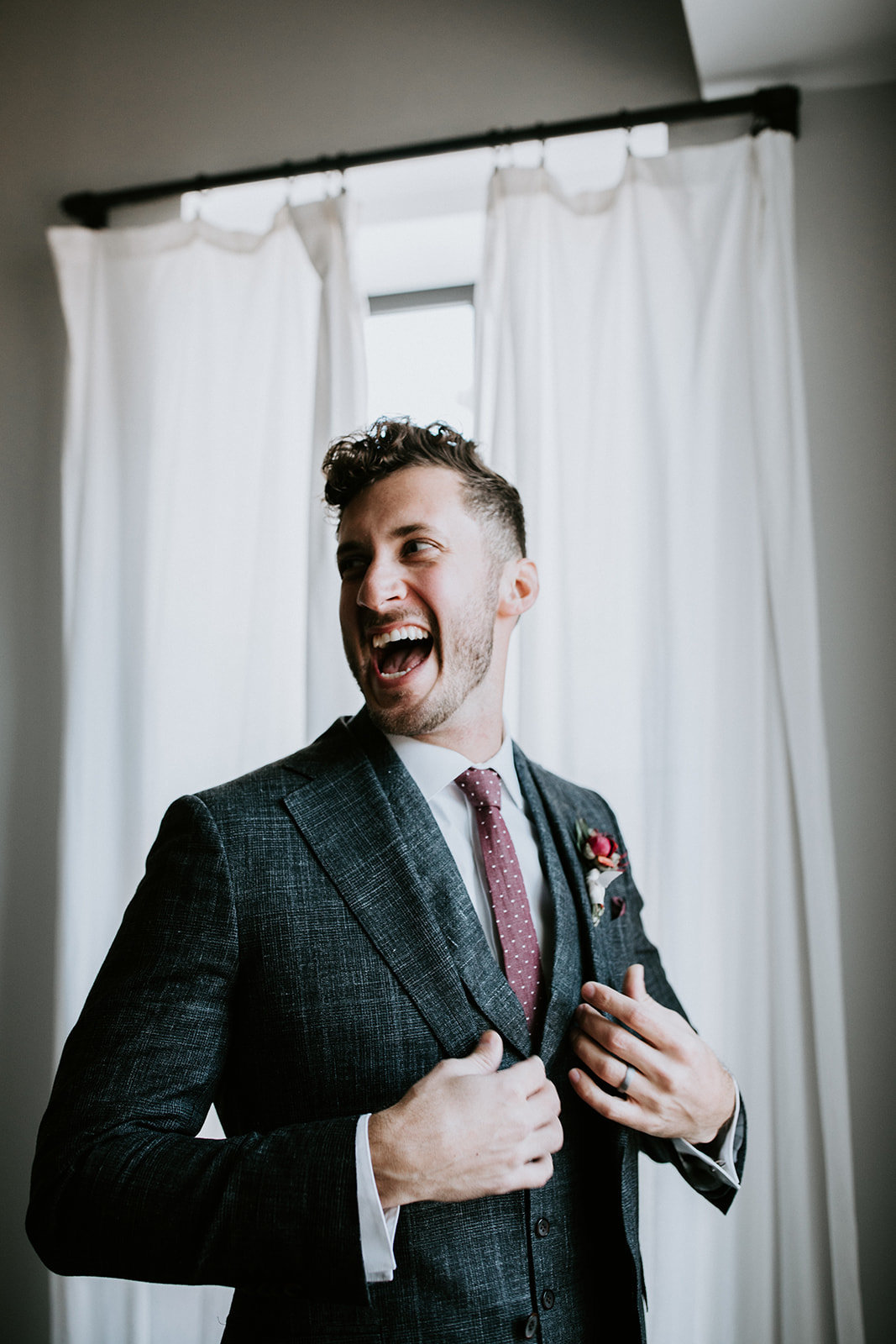 A groom looks away and laughs.