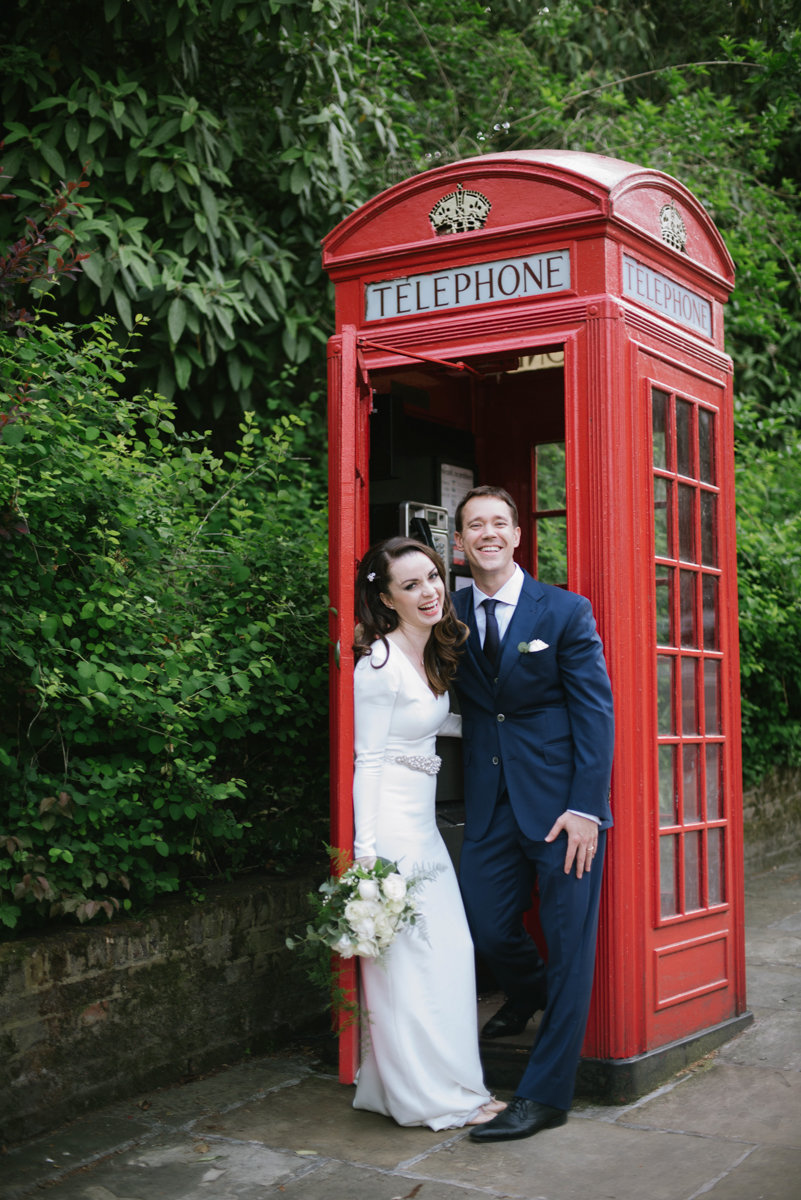 Laughing newlywed couple in a london phone booth